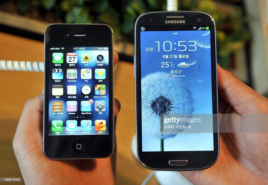 An employee shows an Apple's iPhone 4s (L) and a Samsung's Galaxy S3 (R) at a mobile phone shop in Seoul on August 27, 2012. Shares in Samsung Electronics opened 6.75 percent lower on August 27, 2012 after a US court fined the South Korean firm 1.05 billion USD for breaching Apple's patents. AFP PHOTO / JUNG YEON-JE