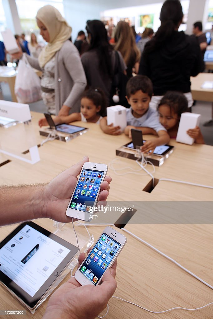 An employee shows Apple's iPhone 5 smartphones in a new Apple store on July 6, 2013 in Rosny-sous-Bois, near Paris. AFP PHOTO / THOMAS SAMSON