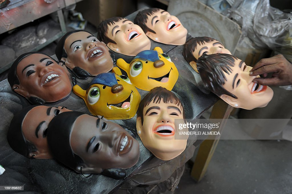 An employee shows masks of Brazilian football stars Neymar and Ronaldinho Gaucho, and the mascot of the Brazil 2014 FIFA World Cup, 'Tatu Bola-Fuleco', at the carnival masks factory Condal, in Sao Gonçalo, about 35 km from downtown Rio de Janeiro, on January 9, 2013. Rio's world famous carnival takes place February 9-12.