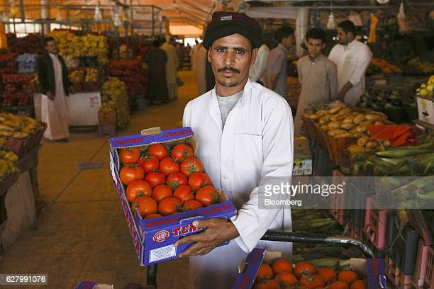 An employee shows off a box of red tomatoes whilst standing on a market stall in Riyadh Saudi Arabia on Thursday Dec 1 2016 Saudi Arabia is working...