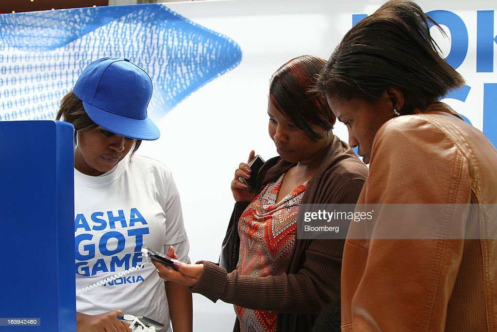 An employee shows shoppers new Nokia Asha smartphones during a promotional 'activation day' event by Nokia Oyj in Maponya Mall in Soweto, South Africa, on Saturday, March 16, 2013. Nokia, based in Espoo, Finland, introduced three phones for its Asha line, sold primarily in emerging markets. Photographer: Nadine Hutton/Bloomberg via Getty Images