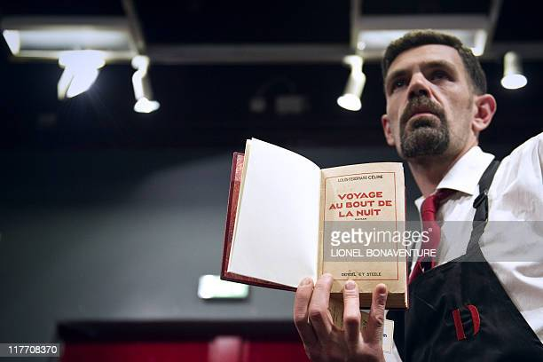 An employee shows the first printed edition of French novelist LouisFerdinand Celine's 'Voyage au bout de la nuit' on June 17 2011 at Paris Drouot...