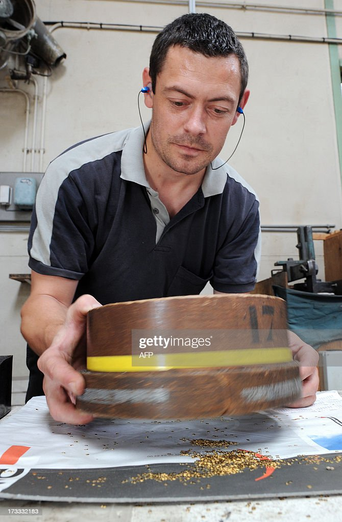 An employee sieves gold glitters, on July 9, 2013, at the B-BA plant, a subsidiary of Marck Group, in La Chartre-sur-le-Loir, western France. B-BA, one of the last in France to maintain, since 1848, the art of traditional military trimmings, manufactures the braids, badges and epaulettes worn during Bastille Day.