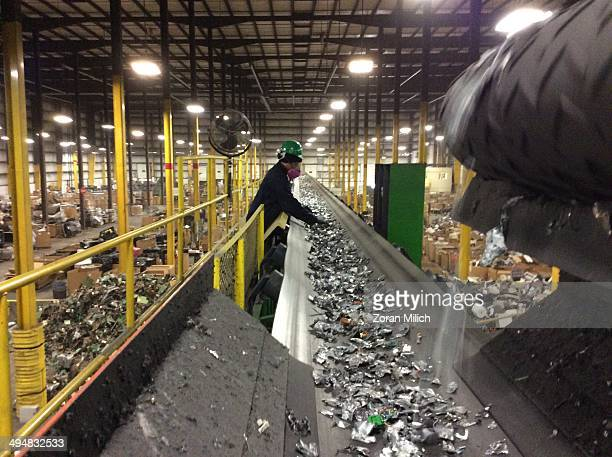 An employee sifts through crushed metal parts dismantled and on a conveyer belt as electronic recyclable waste at the Electronic Recyclers...