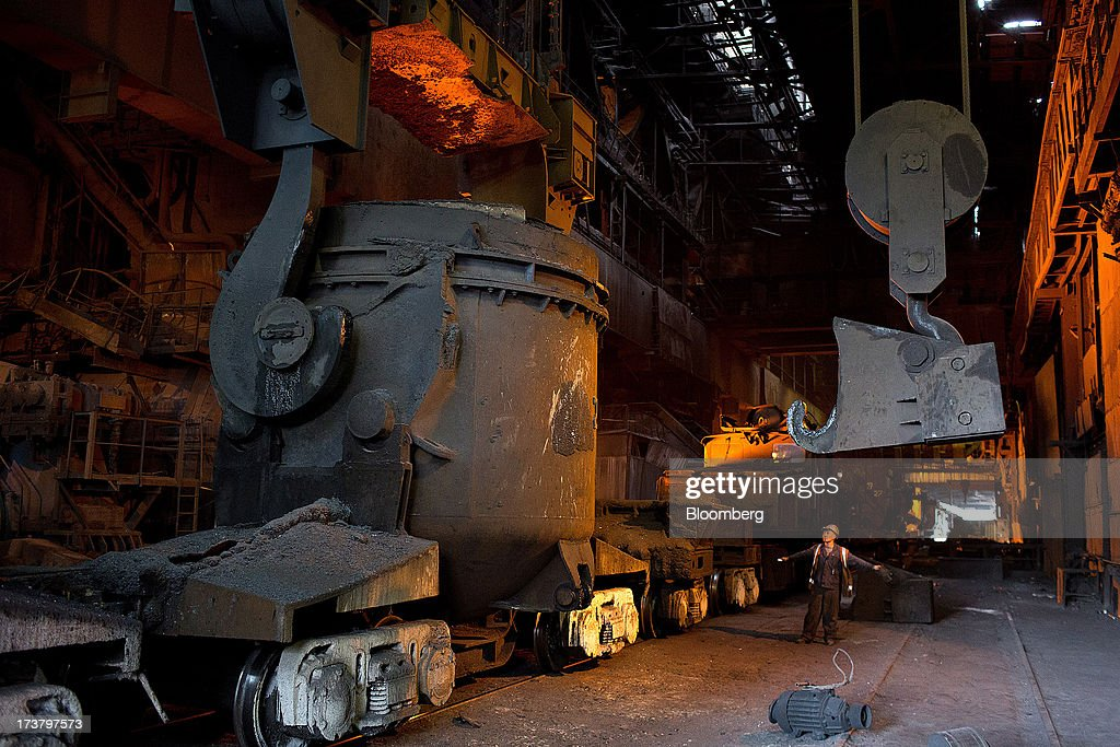 An employee signals to a crane operator during the loading of molten metal into a cauldron aboard a rail wagon in the converter shop at OAO Mechel's metallurgical plant in Chelyabinsk, Russia, on Wednesday, July 17, 2013. Mechel, the country's largest producer of coking coal for steelmakers has begun operating its $700m rail production line which can produce 100 meter rails. Photographer: Andrey Rudakov/Bloomberg via Getty Images