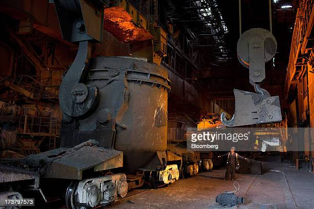 An employee signals to a crane operator during the loading of molten metal into a cauldron aboard a rail wagon in the converter shop at OAO Mechel's...