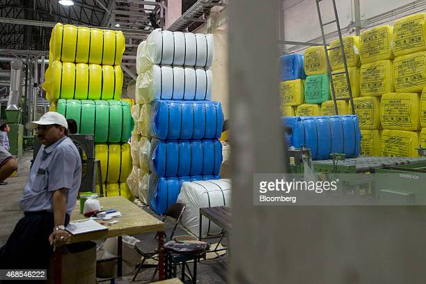 An employee sit near bales of polyester staple fibre at the Indorama Polyester Industries Pcl Nakhon Pathom polyester facility operated by Ventures...