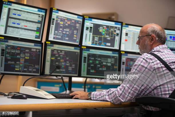 An employee sits at a bank of computer monitors inside the acrylic acid plant control room at the Evonik Industries AG facilities in Marl Chemical...