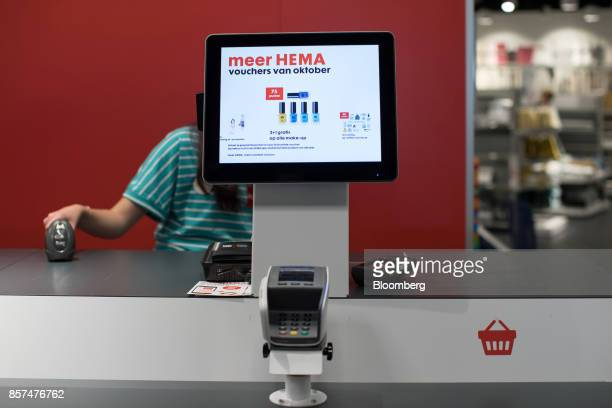 An employee sits at a checkout counter inside a Hema BV store in Tilburg Netherlands on Wednesday Oct 4 2017 Privateequity firm Lion Capital LLP...