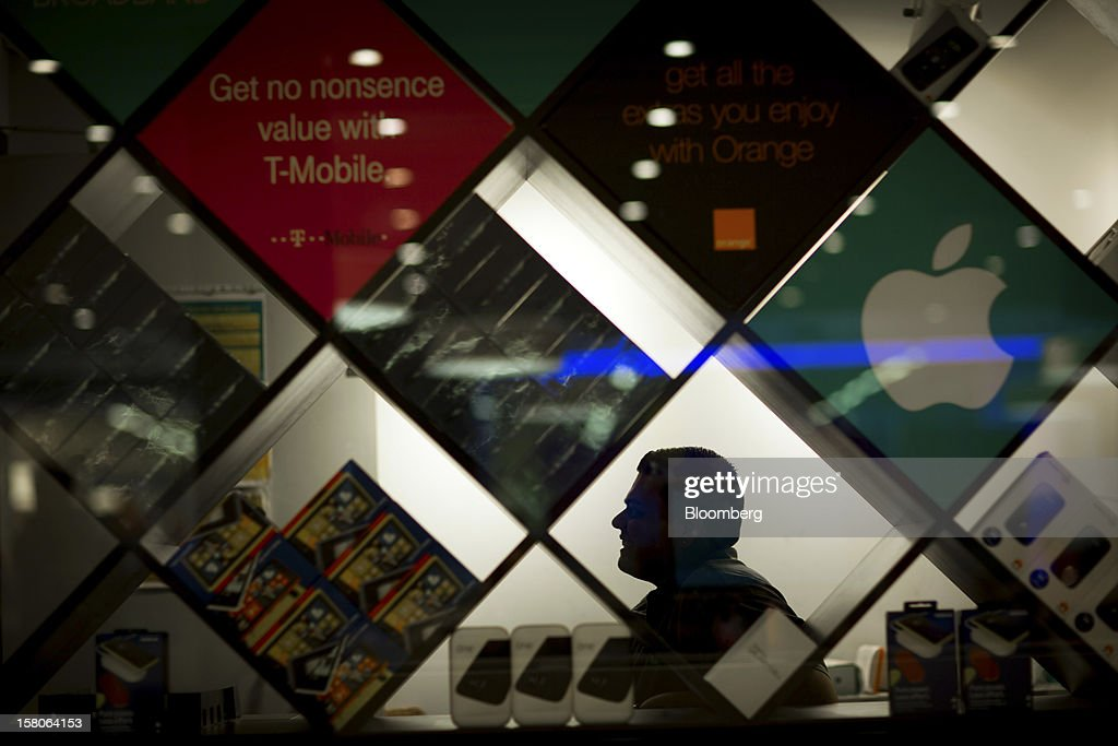 An employee sits behind a display of 4G handsets inside a EE (Everything Everywhere) store, a joint venture between France Telecom SA and Deutsche Telekom AG, in Stratford, U.K., on Monday, Dec. 5, 2012. France Telecom CEO Stephane Richard said in an interview last month that the Paris-based company has received interest from private-equity firms seeking a minority stake in the 50-50 venture, and may also consider an initial public offering of the unit. Photographer: Jason Alden/Bloomberg via Getty Images
