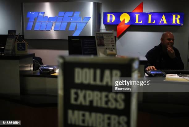 An employee sits behind a Dollar Thrifty Automotive Group Inc rental counter inside Louisville International Airport in Louisville Kentucky US on...