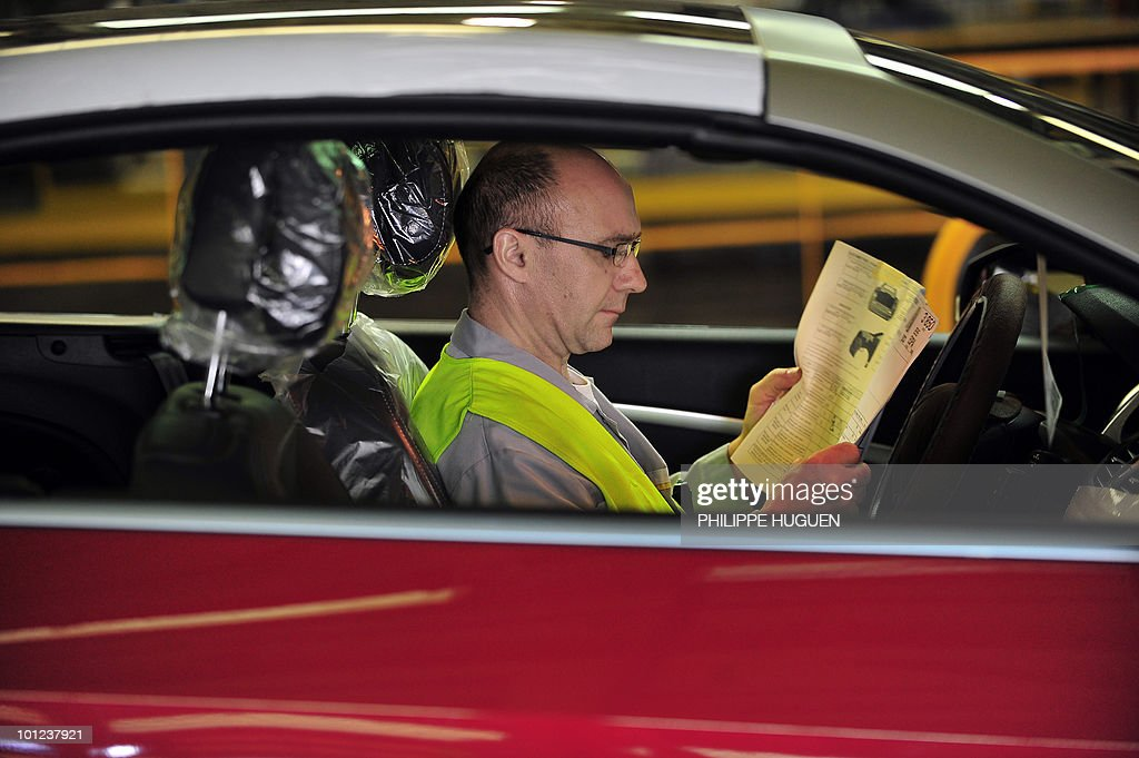 An employee sits in a car on the assembly line of a plant of French carmaker Renault on May 25, 2010 in Douai, northern France.