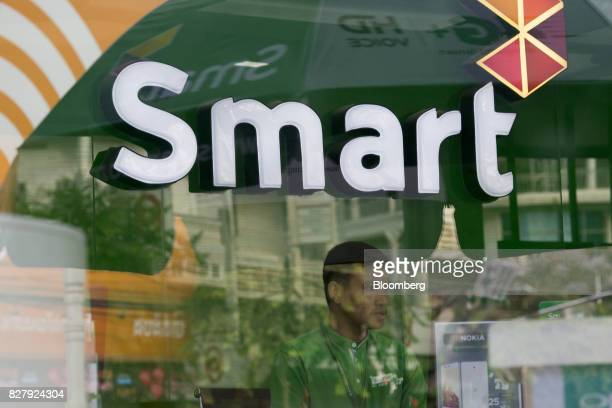 An employee sits inside a Smart Axiata Co store in Battambang Cambodia on Monday Aug 7 2017 The Association of Southeast Asian Nations has much to...