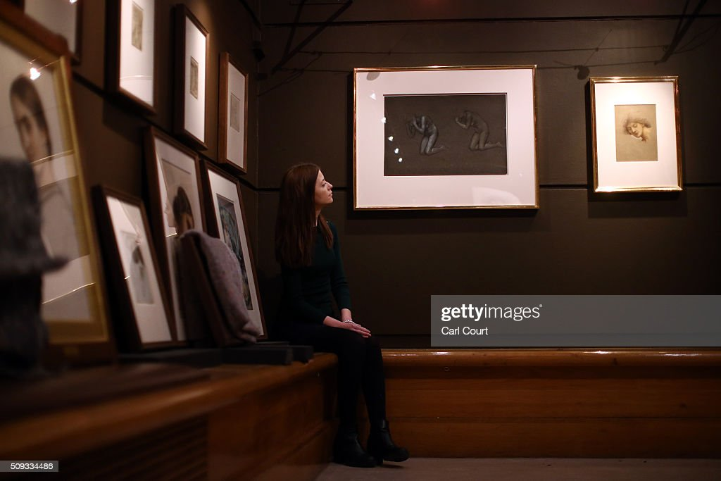 An employee sits next to paintings named 'Two Kneeling Female Nudes, Studies for The Captives' (L) and 'Study of a Female Head for Daughters of the Mist', both by Evelyn De Morgan during a preview at Leighton House Museum on February 10, 2016 in London, England. The work forms part of the Pre-Raphaelites on Paper exhibition, which will run from 12th February to 29th May 2016.