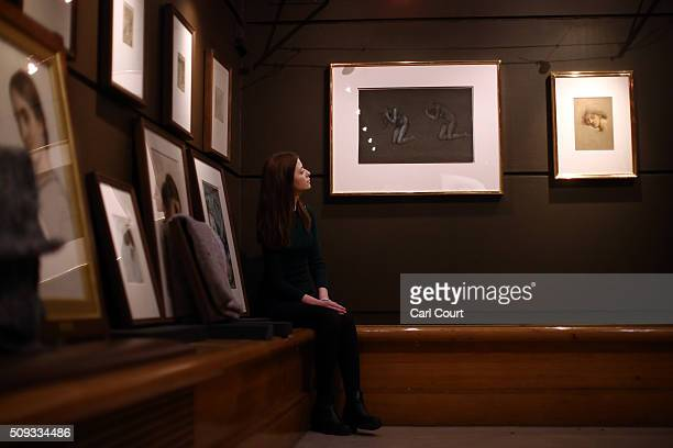 An employee sits next to paintings named 'Two Kneeling Female Nudes Studies for The Captives' and 'Study of a Female Head for Daughters of the Mist'...