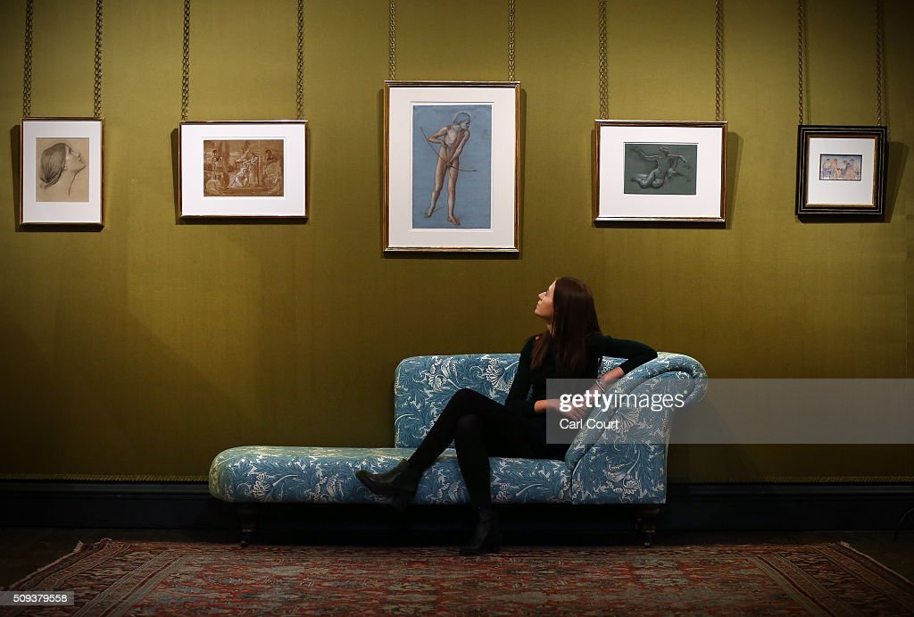 An employee sits on a chaise longue as she poses next to paintings during a preview at Leighton House Museum on February 10, 2016 in London, England. The work forms part of the Pre-Raphaelites on Paper exhibition, which will run from 12th February to 29th May 2016.