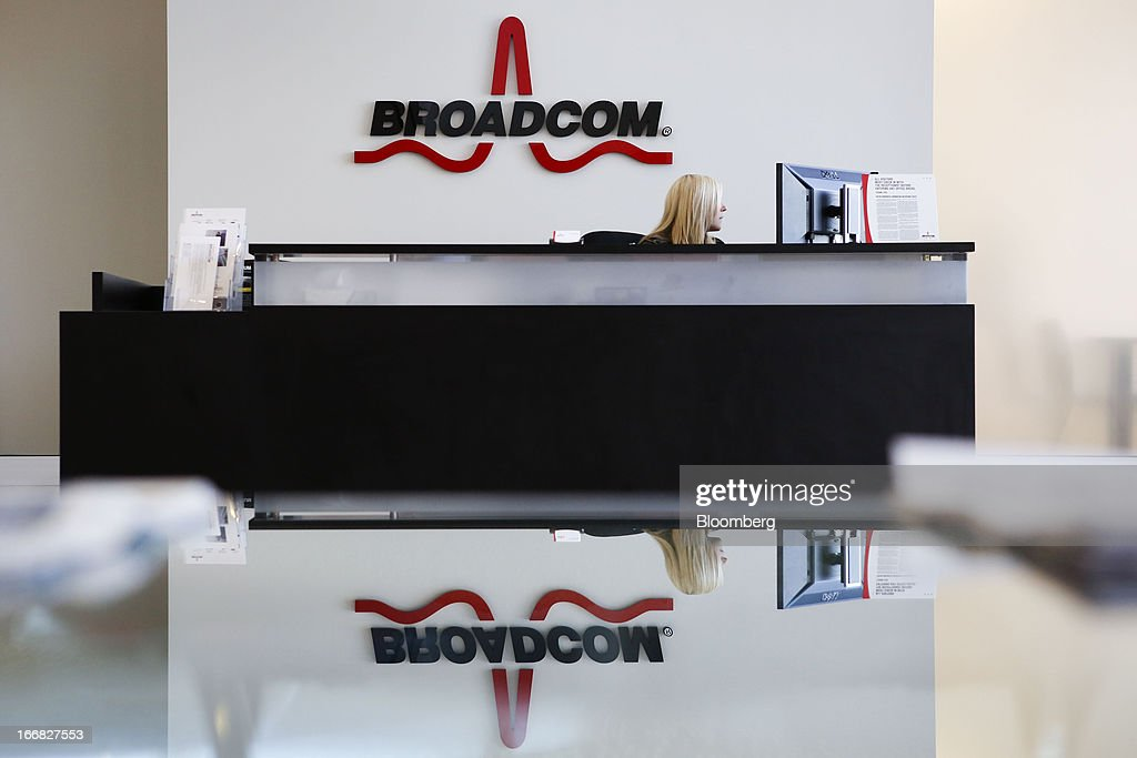 An employee sits under Broadcom Corp. signage inside the lobby of the company's headquarters in Irvine, California, U.S., on Friday, April 12, 2013. Broadcom Corp. designs, develops, and supplies integrated circuits for cable set-top boxes, cable modems, high-speed networking, direct satellite and digital broadcast, and digital subscriber line. Photographer: Patrick Fallon/Bloomberg via Getty Images
