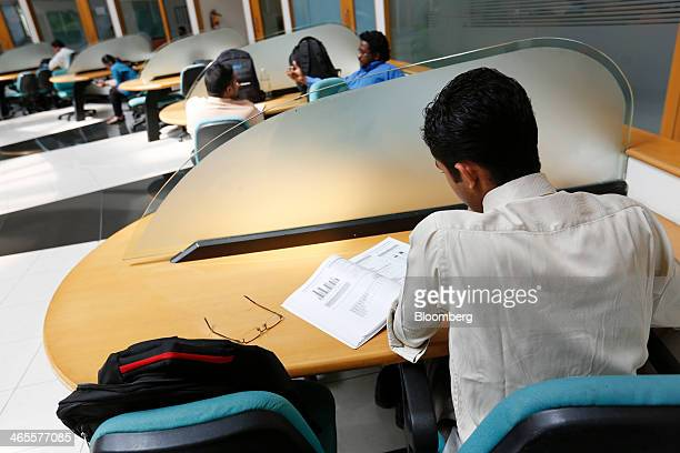 An employee sits working in the library at the Infosys Ltd campus in Electronics City in Bangalore India on Monday Jan 27 2013 Infosys India's...