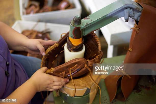 An employee softens the leather of a ball glove at the Nokona manufacturing facility in Nocona Texas US on Thursday July 27 2017 Since the Great...