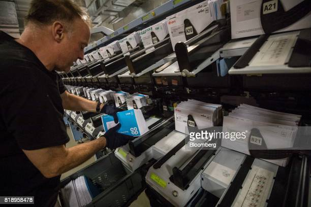 An employee sorts letters processed through an automated sorting machine at the Mount Pleasant post sorting office operated by Royal Mail Plc in...