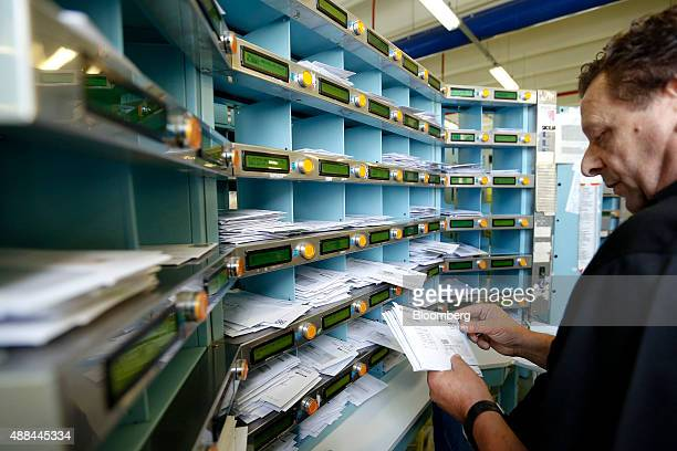 An employee sorts mail by hand inside a Poste Italiane SpA postal sorting office in Fiumicino near Rome Italy on Tuesday Sept 15 2015 Italy is...
