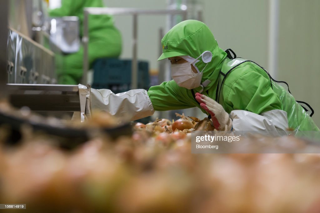 An employee sorts onions at the E-Mart Co. Fresh Center, a sorting facility, in Icheon, South Korea, on Wednesday, Nov. 21, 2012. South Korea's household debt rose to a record in the third quarter as borrowing increased to finance homes and consumption. Photographer: SeongJoon Cho/Bloomberg via Getty Images