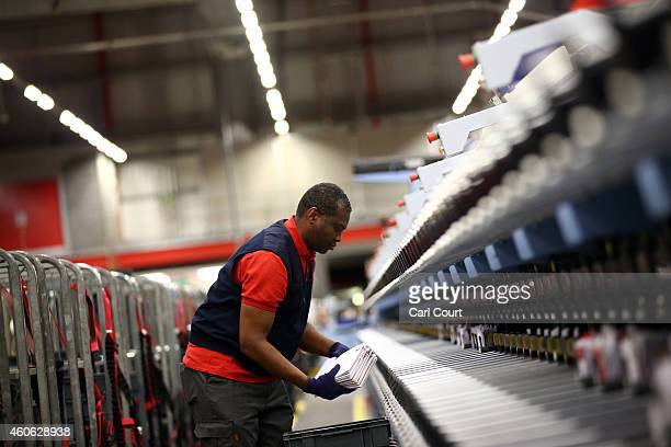 An employee sorts through mail on December 17 2014 in Northampton England This week is expected to be the busiest of the year for Royal Mail as they...