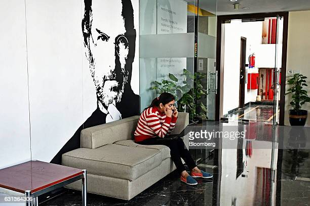 An employee speaks on a mobile phone in front of an image of Steve Jobs cofounder and former chief executive officer of Apple Inc at the office of...