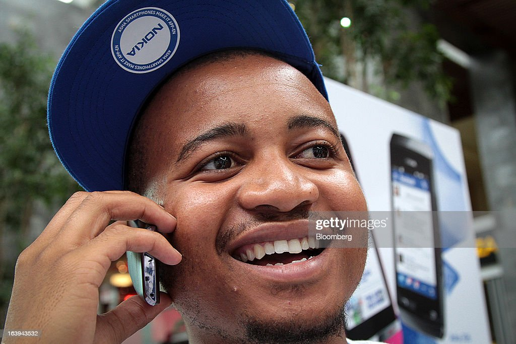 An employee speaks on a Nokia Asha 306 handset during a promotional 'activation day' event by Nokia Oyj in Maponya Mall in Soweto, South Africa, on Saturday, March 16, 2013. Nokia, based in Espoo, Finland, introduced three phones for its Asha line, sold primarily in emerging markets. Photographer: Nadine Hutton/Bloomberg via Getty Images