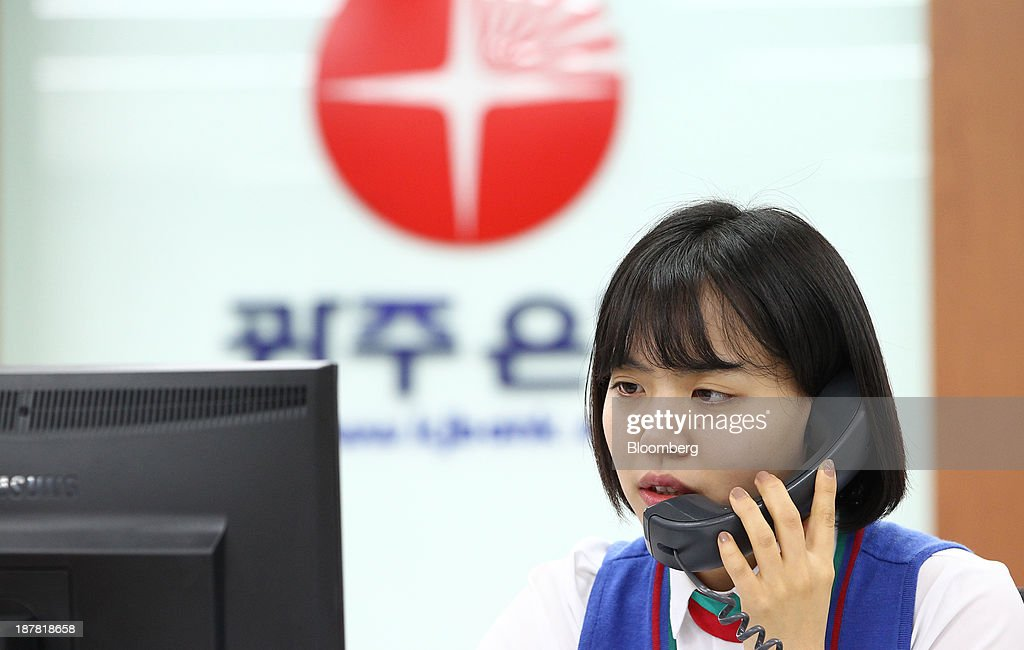 An employee speaks on the telephone at a branch of Kwangju Bank, a unit of Woori Finance Holdings Co., in Seoul, South Korea, on Tuesday, Nov. 12, 2013. Woori Finance Holdings is scheduled to report third-quarter results on Nov. 14. Photographer: SeongJoon Cho/Bloomberg via Getty Images
