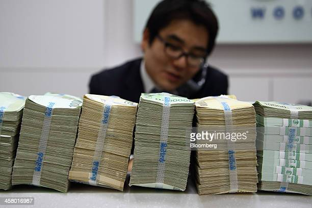 An employee speaks on the telephone behind stacked South Korean won banknotes at a Woori Bank Co branch in Seoul South Korea on Thursday Dec 19 2013...
