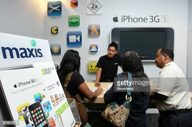 An employee speaks to customers at the Maxis service center in Kuala Lumpur City Centre in Kuala Lumpur Malaysia on Friday Nov 6 2009 Maxis...