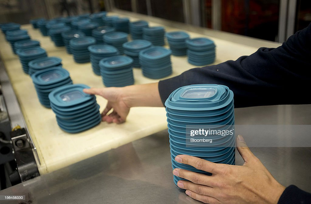 An employee stacks blue food container lids as they come down a conveyor belt after exiting a molding machine at the Newell Rubbermaid Inc. factory in Mogadore, Ohio, U.S., on Thursday, Nov. 15, 2012. The U.S. Federal Reserve is scheduled to release monthly industrial production data on Nov. 16. Photographer: Ty Wright/Bloomberg via Getty Images