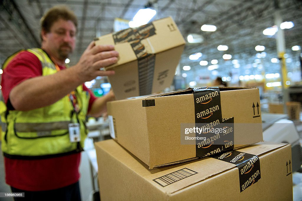 An employee stacks boxes filled with merchandise for shipment at the Amazon.com Inc. distribution center in Phoenix, Arizona, U.S. on Monday, Nov. 26, 2012. U.S. retailers are extending deals into Cyber Monday and beyond to try to sustain a 13 percent gain in Thanksgiving weekend sales. Photographer: David Paul Morris/Bloomberg via Getty Images