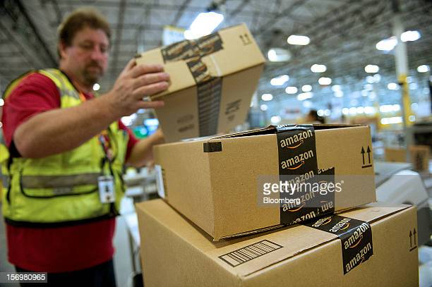 An employee stacks boxes filled with merchandise for shipment at the Amazoncom Inc distribution center in Phoenix Arizona US on Monday Nov 26 2012 US...