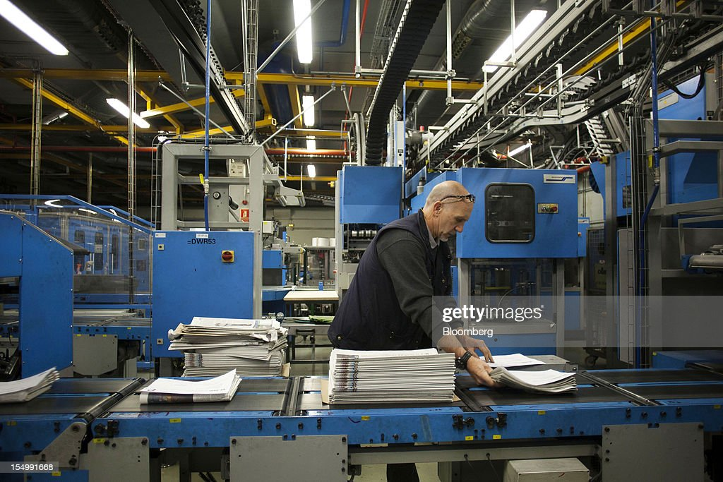 An employee stacks bundles of El Pais daily newspapers for distribution at the El Pais printing plant in Madrid, Spain, on Tuesday, Oct. 30, 2012. Prisa, the publisher of El Pais newspaper, has announced staff reductions and salary cuts. Photographer: Angel Navarrete/Bloomberg via Getty Images