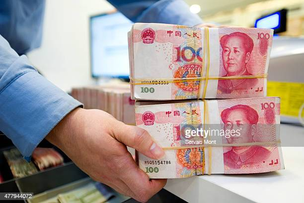 An employee stacks Chinese Yuan bank notes in a Standard Chartered bank branch on May 13 in Shanghai China Aiming for more access to the global...