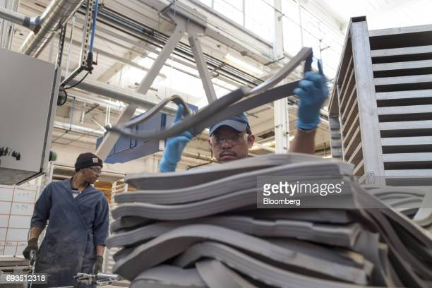 An employee stacks clay to be shaped into tile pieces at the Heath Ceramics Ltd production facility in San Francisco California US on Friday June 2...