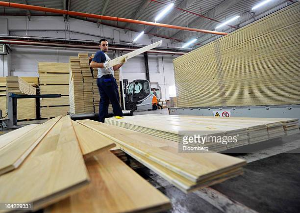 An employee stacks completed sections of multilayer wooden parquet flooring in the warehouse at Tarkett SA's factory in Backa Palanka Serbia on...