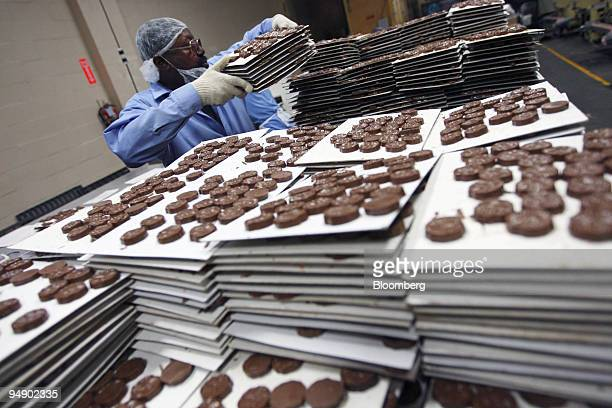 An employee stacks sheets of cooled chocolate at the kosher certified Madelaine Chocolate Novelties Inc factory in the Queens borough of New York US...