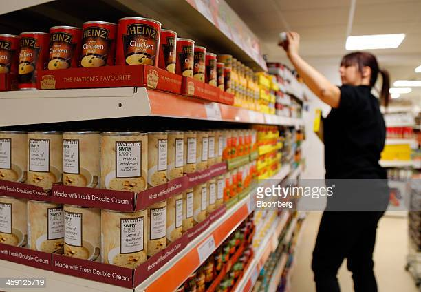 An employee stacks shelves as tins of soup manufactured by HJ Heinz Co and Marks Spencer Group Plc sit on sale inside the Community shop a...