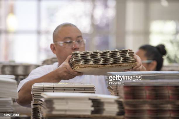 An employee stacks tile pieces to be packaged at the Heath Ceramics Ltd production facility in San Francisco California US on Friday June 2 2017 The...