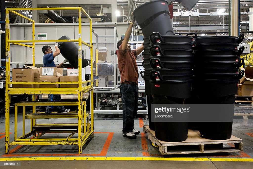 An employee stacks trash cans as hey come out of the molding machine at the Newell Rubbermaid Inc. factory in Mogadore, Ohio, U.S., on Thursday, Nov. 15, 2012. The U.S. Federal Reserve is scheduled to release monthly industrial production data on Nov. 16. Photographer: Ty Wright/Bloomberg via Getty Images