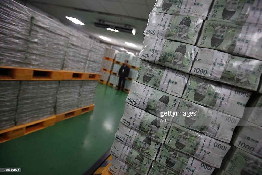 An employee standing amongst stacks of South Korean won for delivery to commercial banks at the Bank of Korea's headquarters in Seoul on February 5, 2013. Cash demand usually picks up ahead of the Lunar New Year holiday, which begins February on 10, as companies give out special cash bonuses to their employees and parents give money to their children. AFP PHOTO / POOL / Kim Hong-Ji