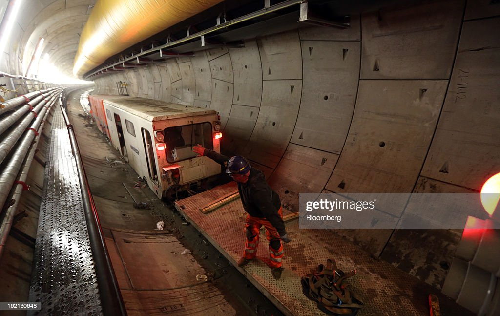 An employee stands aboard a works locomotive inside one of new western tunnels, developed by Crossrail, beneath London, U.K., on Tuesday, Feb. 19, 2013. Network Rail Ltd. projects include a 6 billion-pound upgrade to the Thameslink line that spans London from north to south and the Crossrail project to build an east-west line through the capital, Finance Director Patrick Butcher said. Photographer: Chris Ratcliffe/Bloomberg via Getty Images