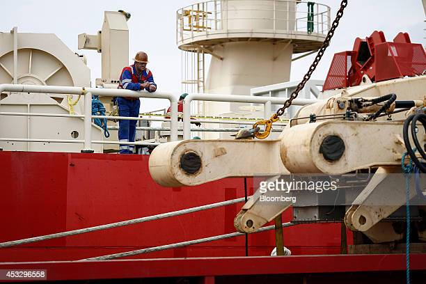 An employee stands aboard the offshore pipelay vessel Deep Energy operated by Technip SA as it sits moored to the dockside of the Cromarty Firth in...