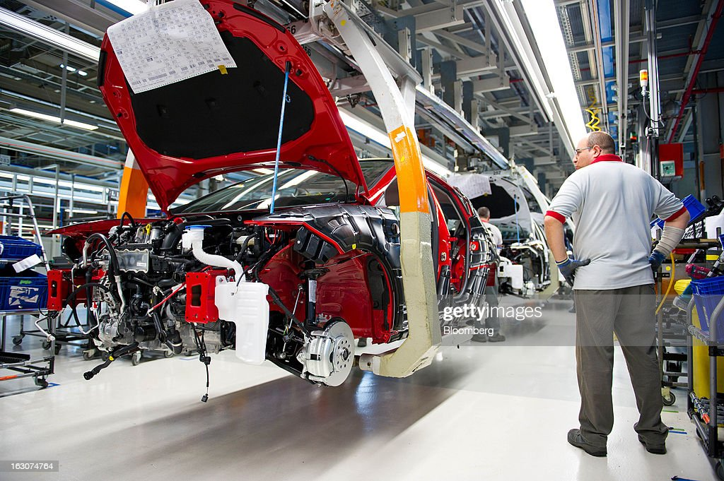 An employee stands and looks at a Seat Altea XL automobile during assembly on the production line at the headquarters of Seat SA in Martorell, Spain, on Thursday Feb. 28, 2013. Seat will invest 300 million euros a year in the next five years and renew its range of models, Efe said, citing an interview with James Muir, head of the Spanish unit of Volkswagen AG. Photographer: David Ramos/Bloomberg via Getty Images
