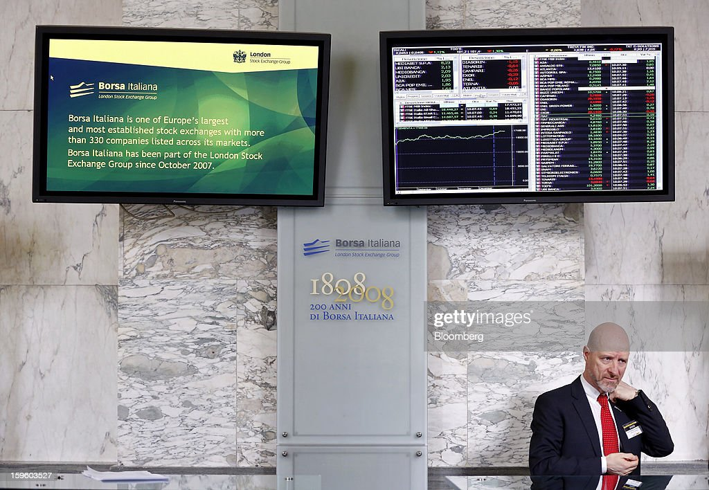 An employee stands at a desk beneath an electronic screen displaying share price information inside the Borsa Italiana, Italy's stock exchange, which is part of the London Stock Exchange Group Plc, in Milan, Italy, on Thursday, Jan. 17, 2013. The euro-area economy won't return to growth until the next quarter as a recovery in Italy is delayed and France continues to shrink, according to a survey of economists. Photographer: Alessia Pierdomenico/Bloomberg via Getty Images