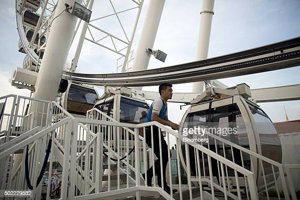 An employee stands at a ferris wheel in the Asiatique The Riverfront openair mall in Bangkok Thailand on Friday Dec 18 2015 Thai economic indicators...
