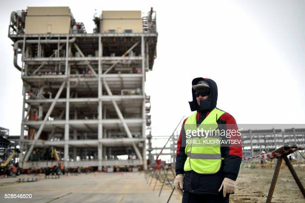 An employee stands at the construction site of a gas processing plant at the port of Sabetta in the Kara Sea shore line on the Yamal Peninsula in the...